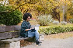 Professional black woman working with laptop outside in autumn. Stylish black female entrepreneur working with modern convertible laptop outdoor in autumn at royalty free stock photo
