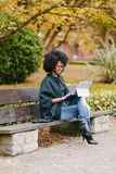 Professional black woman working with laptop outside in autumn. Stylish black female entrepreneur working with modern convertible laptop outdoor in autumn at royalty free stock photos