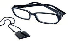 Stylish Black glasses and pendant with ball chain. Stylish, modern, black eyewear and necklace display isolated on white Stock Image