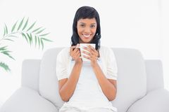 Stylish black haired woman in white clothes enjoying coffee Stock Images