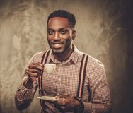 Stylish black man with cup of coffee posing on dark background. Royalty Free Stock Image