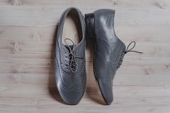 Stylish black mens crafted shoes for ballroom dancing. Stylish gray mens crafted shoes for ballroom dancing with laces from skin and suede on the wooden Royalty Free Stock Image
