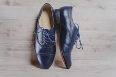 Stylish black mens crafted shoes for ballroom dancing. Stylish blue mens crafted shoes for ballroom dancing with laces from skin and suede on the wooden royalty free stock photos