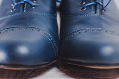 Stylish black mens crafted shoes for ballroom dancing. Stylish blue mens crafted shoes with laces from skin and suede. macro photography of crafted mens blue Stock Image