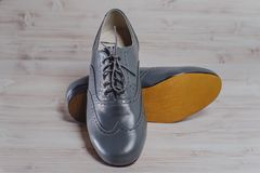 Stylish black mens crafted shoes for ballroom dancing. Stylish gray mens crafted shoes for ballroom dancing with laces from skin and suede on the wooden Royalty Free Stock Photos