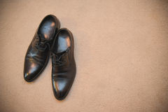 Stylish black shoes. Lying on a brown rug Royalty Free Stock Photos