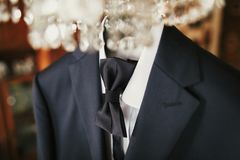 Stylish black suit with white shirt and bow tie on hanger on lux. Ury chandelier. morning preparations before wedding day. groom outfit Royalty Free Stock Photography