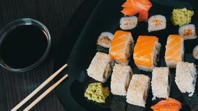 Stylish black sushi set on flat plate with different kinds of roll, nigiri, maki, gunkan. Japanese national cuisine. Stylish black sushi set on a flat plate with stock video footage