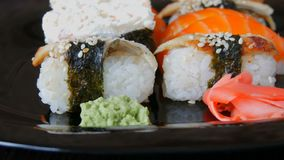 Stylish black sushi set on flat plate with different kinds of roll, nigiri, maki, gunkan. Japanese national cuisine. Stylish black sushi set on a flat plate with stock footage