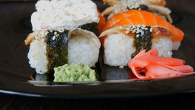Stylish black sushi set on flat plate with different kinds of roll, nigiri, maki, gunkan. Japanese national cuisine. Stylish black sushi set on a flat plate with stock video