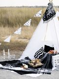Stylish black and white picnic. Stylish black and white picnic on the shore of  northern sea. Classic monochrome plaid, flag, tipi, candles and food Stock Photos