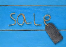 Stylish blank price tag of denim on a string rests on a blue pai Royalty Free Stock Image