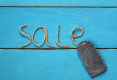 Stylish blank price tag of denim on a string rests on a blue pai Royalty Free Stock Photos