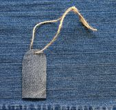 Stylish blank price tag on a rope on the background of denim for Royalty Free Stock Photography