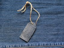 Stylish blank price tag on a rope on the background of denim for Stock Images