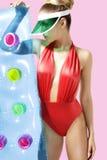 Stylish blond girl posing wearing  beachwear and sunshade Stock Image