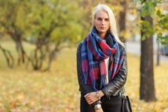 Stylish blond girl in warm plaid scarf in fall season Stock Image