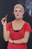 Stylish blond woman smoking an e-cigarette Royalty Free Stock Photo