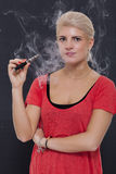 Stylish blond woman smoking an e-cigarette Stock Photos