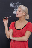 Stylish blond woman smoking an e-cigarette Royalty Free Stock Photography