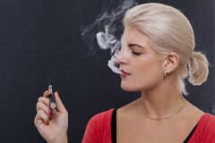 Stylish blond woman smoking an e-cigarette Royalty Free Stock Photos