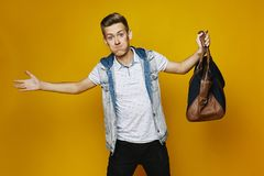 Stylish blond young man in black jeans and white t-shirt, is standing with bag in his hand, isolated at yellow background royalty free stock image