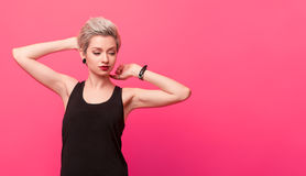 Stylish blond young woman in a retro round sunglasses. Young beautiful attractive blonde woman in round sunglasses on pink background with copy space royalty free stock photos
