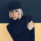 Stylish blonde in black cap and black shirt. Stock Photos