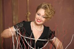 Stylish blonde in a black dress with a pearl necklace Stock Photography