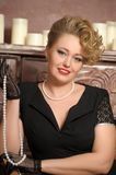 Stylish blonde in a black dress with a pearl necklace royalty free stock photo