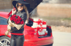 Stylish blonde with a bouquet of red roses Stock Images