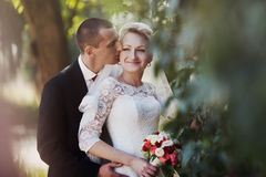 Stylish blonde caucasian happy bride with groom are posing on th Royalty Free Stock Image