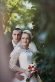 Stylish blonde caucasian happy bride with groom are posing on th Royalty Free Stock Photography
