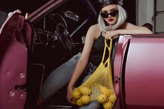 Stylish blonde girl in beret and sunglasses holding string bag with lemons while sitting in car royalty free stock photo
