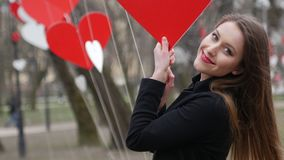 Stylish blonde girl cheerfully smiling and playing with red paper hearts decoration in the autumn park. Valentine's day. Celebration stock footage