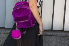 Stylish blonde girl in dress walking at the city with a little purple backpack. Empty space royalty free stock photo