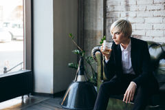 Stylish blonde girl drinking alcohol in a cafe Royalty Free Stock Photos