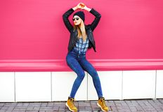 Stylish blonde girl model in full-length posing wearing rock black style jacket, hat on city street over colorful pink wall royalty free stock photo