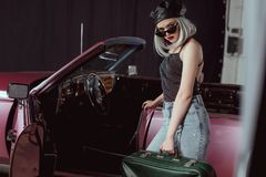 Stylish blonde girl in sunglases and beret holding retro suitcase and looking at camera while standing near maroon. Car stock photography