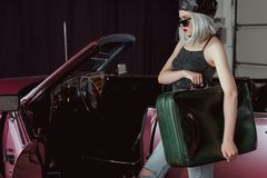Stylish blonde girl in sunglases and beret holding retro suitcase while standing near maroon. Car royalty free stock photos