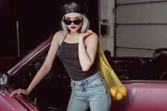 Stylish blonde girl in sunglasses and beret holding string bag with lemons and looking at camera while standing near car stock photo