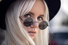 Stylish blonde girl in sunglasses outside Royalty Free Stock Photography