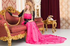 Stylish blonde in long red dress is sitting on luxurious  sofa. Stylish blonde in long red dress is sitting on luxurious sofa Stock Photography