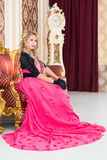 Stylish blonde in long red dress is sitting on luxurious  sofa. Stylish blonde in long red dress is sitting on luxurious sofa Stock Images
