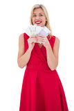 Stylish blonde in red dress holding cash Stock Photos