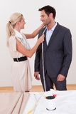 Seamstress measuring a man for a suit Royalty Free Stock Photography