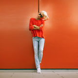 Stylish blonde stand near red wall on city street. Stock Photography
