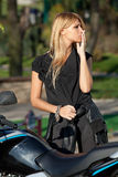 Stylish blonde standing near motorcycle Stock Image