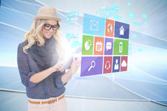 Stylish blonde using tablet pc with app icon menu Royalty Free Stock Image