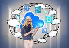 Stylish blonde using tablet pc with app icons and cloud Royalty Free Stock Image